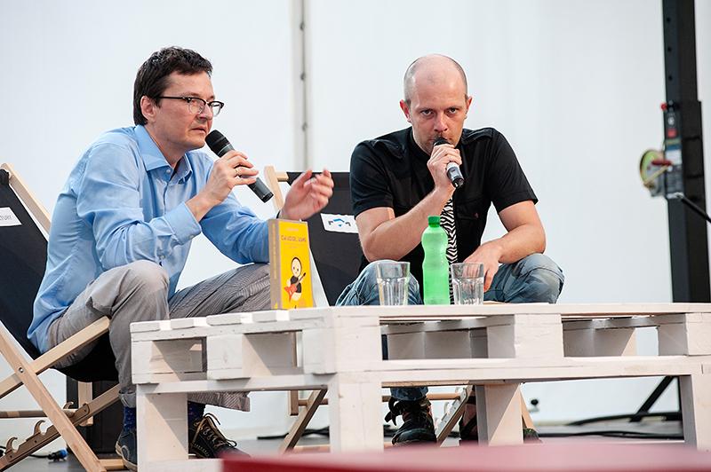 [Zdjęcie z dyskusji. Widać dwóch mężczyzn, którzy siedzą na czarnych leżakach, przy białym niskim stoliku, na którym stoi książka. W rękach trzymają mikrofony.]