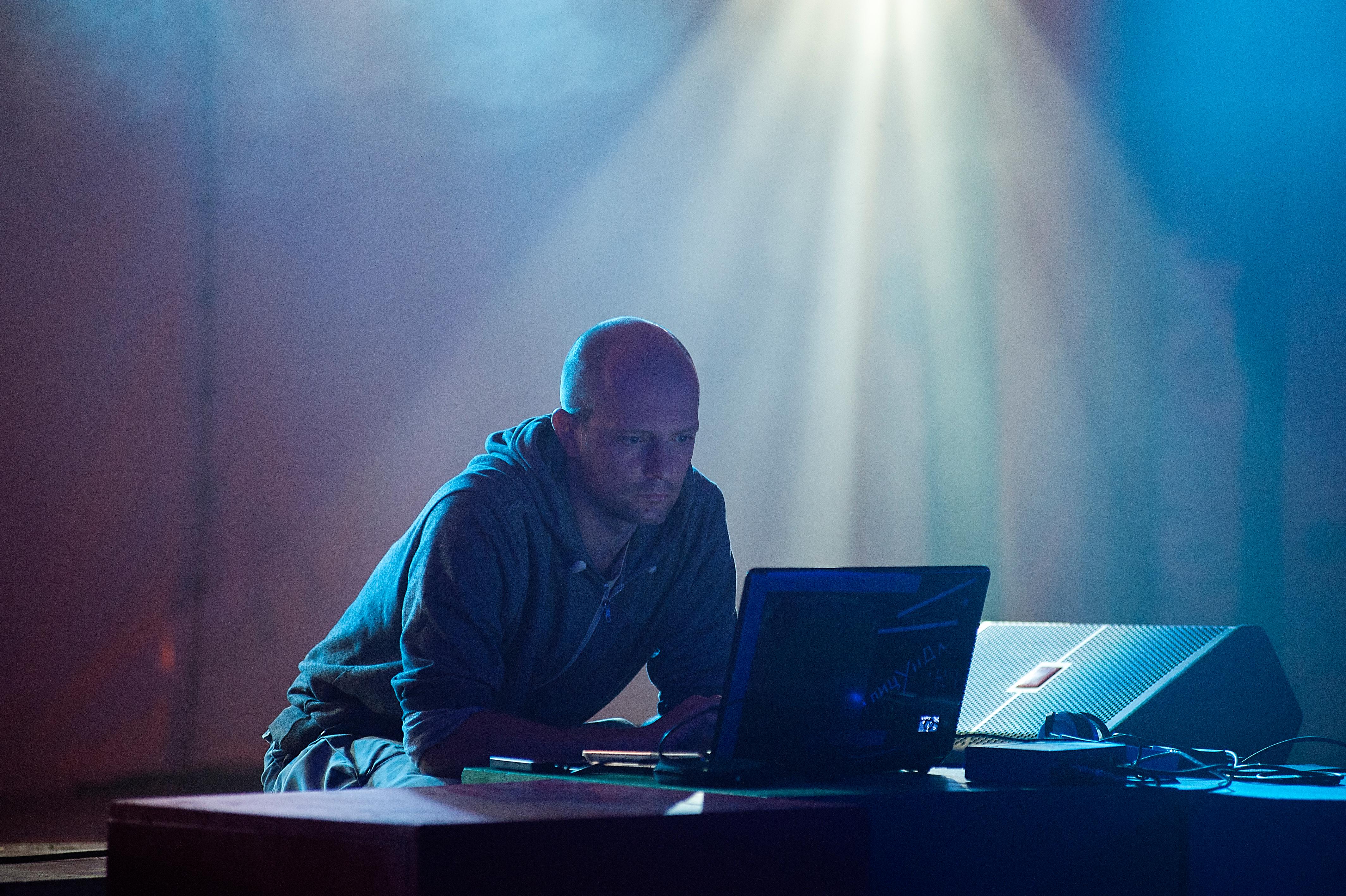 Zdjęcie z koncertu zespołu Konstanty Usenko – set DJski, przedstawiające młodego mężczyznę, siedzącego na scenie i patrzącego w monitor laptopa.