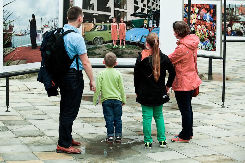 Zdjęcie z Wystawy Eastreet 2 przedstawiające dwoje dorosłych (mężczyznę i kobietę) oraz dwoje dzieci (dziewczynkę i chłopca) oglądających panel wystawy plenerowej.
