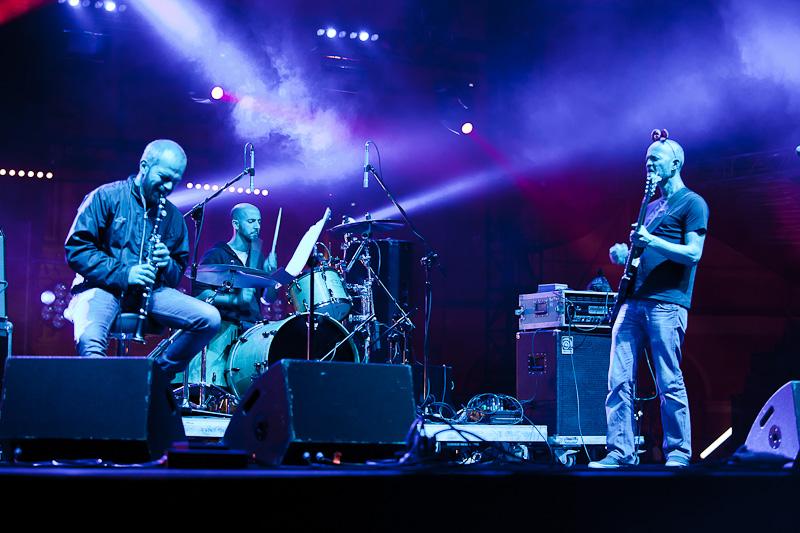 Zdjęcie z koncertu zespołu Kruzenshtern & Parohod przedstawiające trzech mężczyzn na scenie, którzy grają na perkusji, gitarze eleketrycznej oraz klarnecie.  fot. R. Pranagal