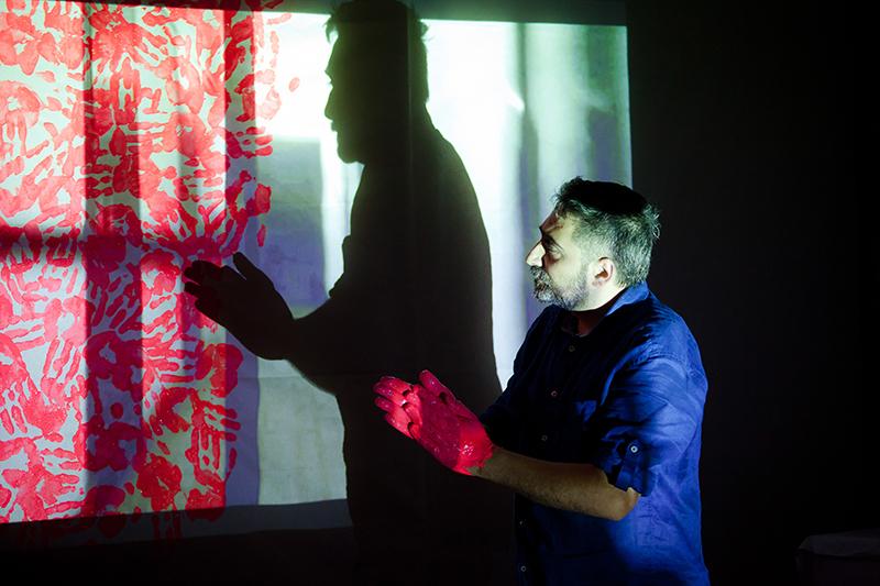 """Zdjęcie z wydarzenia Waldemar Tatarczuk/Narek Avetisjan – Performance """"22 lata później"""" przedstawiające mężczyznę, który odbija swoje dłonie w czerwonej farbie na płótnie."""