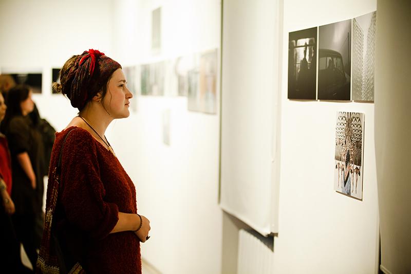 Zdjęcie z Wystawy Eastreet 2 przedstawiające na pierwszym planie młodą kobietę w bordowym swetrze i bordowej opasce na upiętych włosach, która ogląda plansze wystawy wewnętrznej. W tle inni zwiedzający. fot. R. Pranagal
