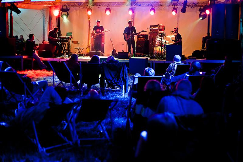 [Zdjęcie z koncertu zespołu Soft Eject. Na pierwszym planie, w granatowej poświacie siedzi na leżakach publiczność, w tle scena z muzykami.]