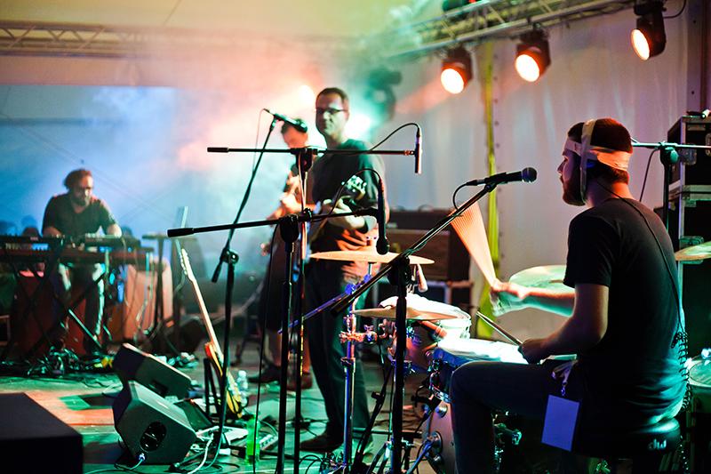 [Na zdjęciu z koncertu zespołu Soft Eject widać muzyków na scenie, którzy grają na perkusji, gitarze i klawiszach.]