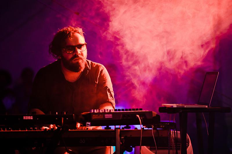 [Zdjęcie z koncertu Soft Eject. Na pierwszym planie mężczyzna w okularach grający na klawiszach, na scenie, na tle ciemnoróżowej mgły.]
