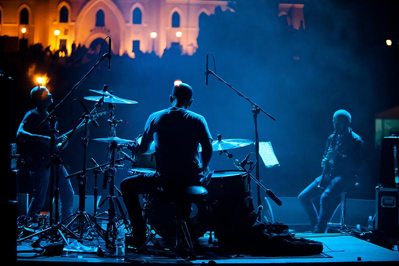 Zdjęcie z koncertu zespołu Kruzenshtern & Parohod przedstawiające trzech muzyków, którzy grają na perkusji, gitarze elektrycznej i klarnecie. W tle podświetlony Zamek Lubelski.