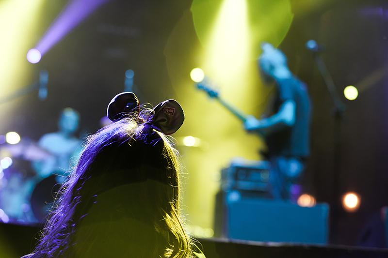 Zdjęcie z koncertu Kruzenshtern & Parohod. Na pierwszym planie głowa fanki, w tle mężczyzna grający na gitarze elektrycznej.