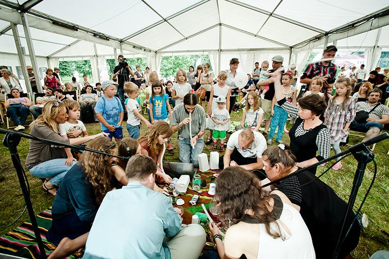 Zdjęcie z Laboratorium Sztuki Społecznej przedstawia młodych dorosłych siedzących w kręgu, obok nich stojące dzieci. Dorośli nachyleni ku sobie są skupieni na jakiś zadaniach.