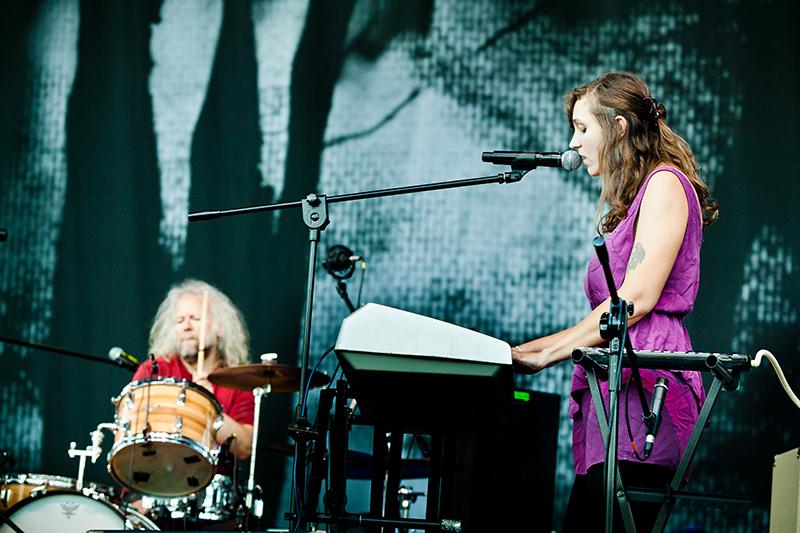 Zdjęcie z koncertu Cheer Accident. Na pierwszym planie młoda kobieta w fioletowej sukience, która śpiewa i gra na keyboardzie. W tle siwy mężczyzna grający na perkusji. , fot. R. Pranagal