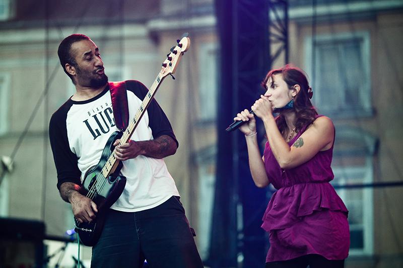 Zdjęcie z koncertu zespołu Cheer Accident. Młoda kobieta w fioletowej sukience śpiewa, obok niej mężczyzna w białej bluzie gra na gitarze. Patrzą na siebie., fot. Robert Pranagal