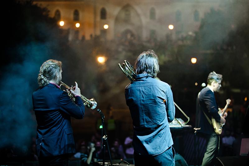 Zdjęcie z koncertu Felix Kubin i Mitch and Mitch przedstawiające trzech muzyków na scenie, tyłem do obiektywu, grają na gitarze, puzonie i trąbce