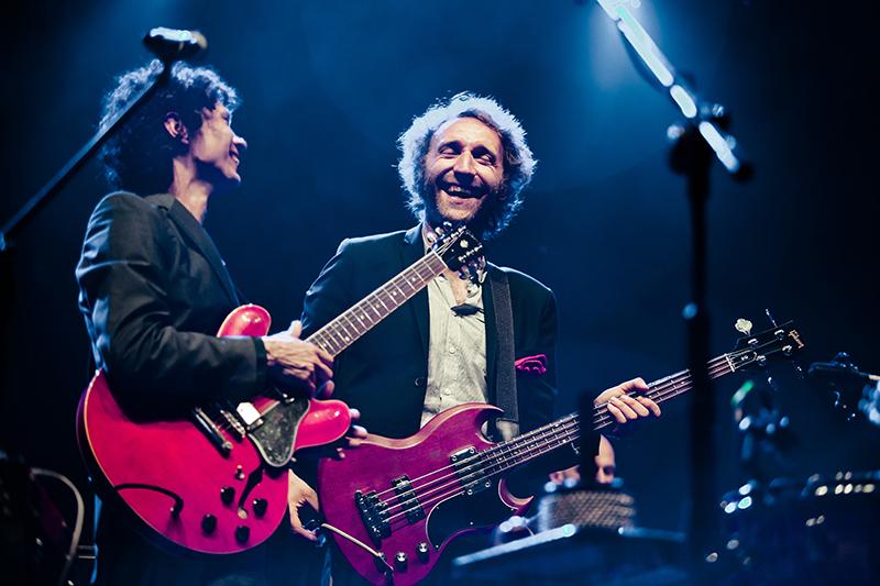 Zdjęcie z koncertu Felix Kubin i Mitch and Mitch, przedstawiające dwóch mężczyzn na scenie, trzymających gitary i śmiejących się do siebie.