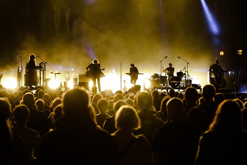 Koncert Goldfrapp. Na pierwszym planie publiczność odwrócona tyłem do obiektywu a przodem do sceny, na której, w złotym świetle gra zespół.l
