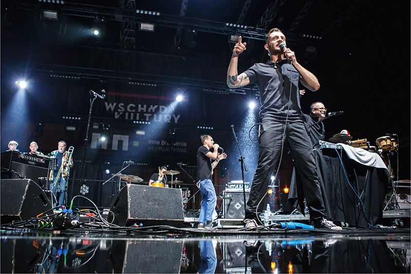 Zdjęcie z koncertu Big Lao Che Band. Na scenie, która z tyłu ma baner z napisem Wschód Kultury Inne Brzmienia występuje zespół.