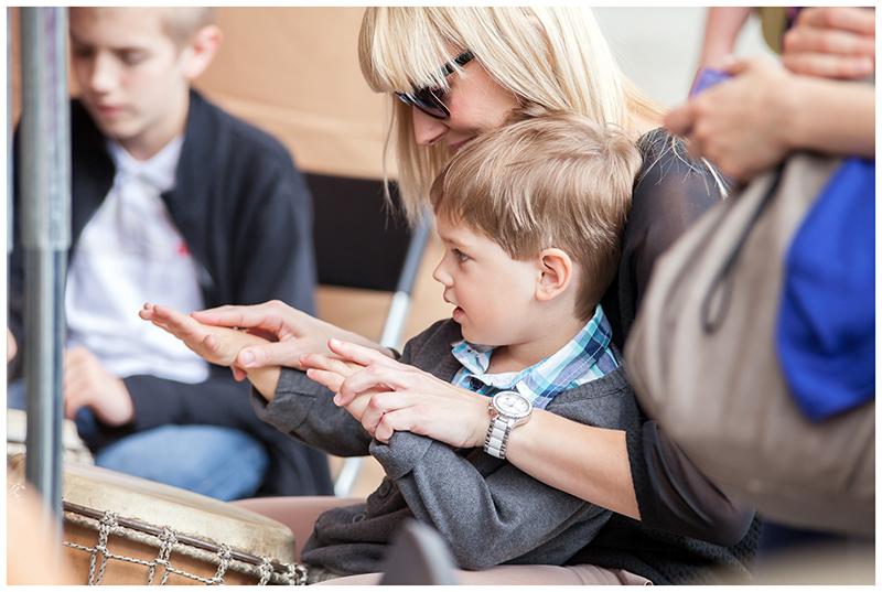 Zdjęcie z Małych Innch Brzmień przedstawiające młodą kobietą, która ma na kolanach małego chłopca grającego na bębnie.