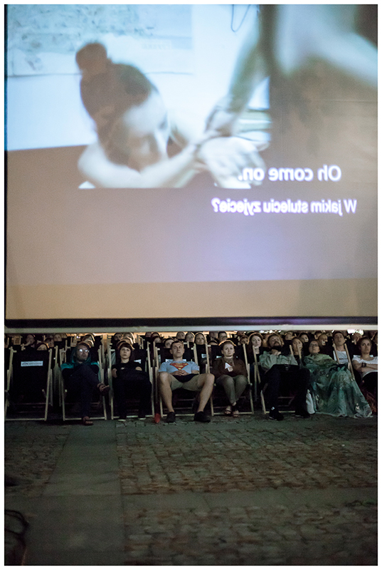 Zdjęcie z projekcji filmu w ramach cyklu Move East Movie przedstawijące publiczność, która siedzi na leżakach oraz fragment ekranu.