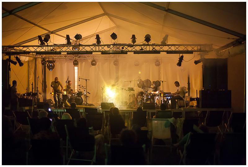 Zdjęcie z koncertu Pafnuty's dream przedstawiające muzyków na scenie oraz publiczność, która siedzi na leżakach pod sceną.