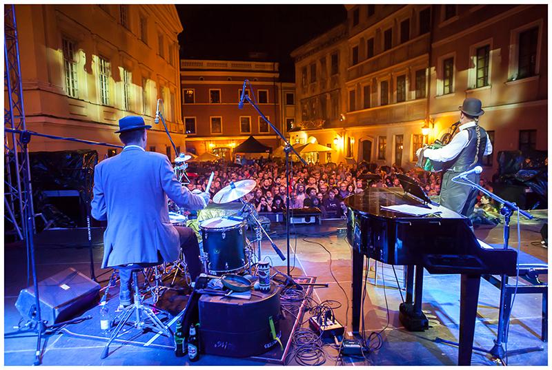 Zdjęcie z koncertu zespołu The Tiger Lillies przedstawiające mężczyzn na scenie, któzy grają na perkusji i akordeonie, w tle publiczność
