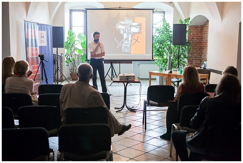 [Zdjęcie z festiwalu Wschód Kultury Inne Brzmienia. W sali widać mężczyznę w białej koszuli, który przedstawia prezentację, bliżej obiektywu, tyłem do niego na krzesłach siedzą słuchacze.]