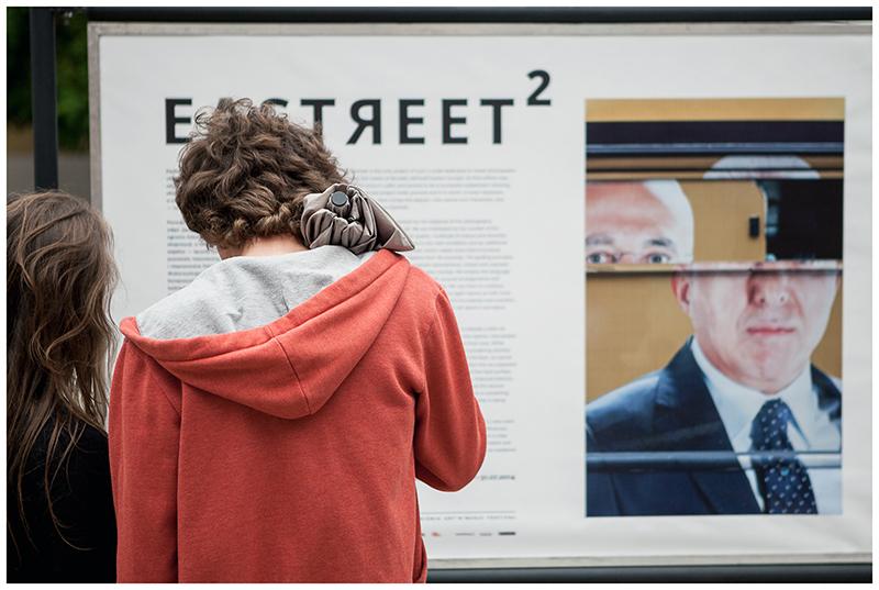 Zdjęcie przedstawia młodego mężczyznę z pomarańczowej bluzie z młodą długowłosą kobietą, którzy oglądają planszę z wystawy Eastreet 2.