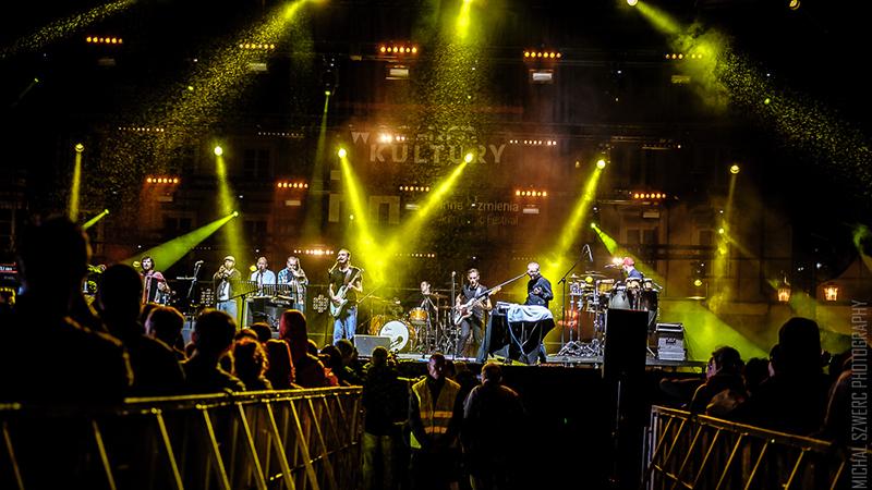 Koncert zespołu Big Lao Che Band. Na scenie spowitej żółtym światłem reflektorów występuje zespół, na pierwszym planie publiczność odwrócona od obiektywu.