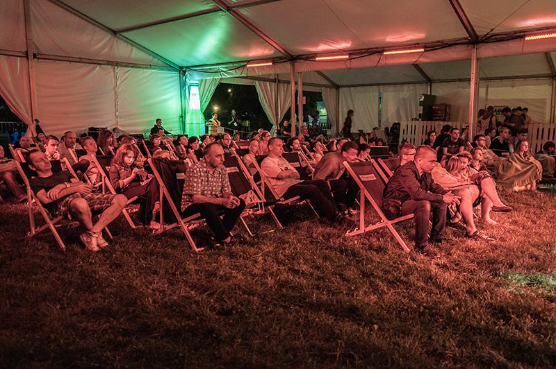 Zdjęcie z koncertu: Elisabeth Harnik, Martin Brandlmay, Mikołaj Trzaska, przedstawiające siedzącą na leżakach pod dużym namiotem publiczność.