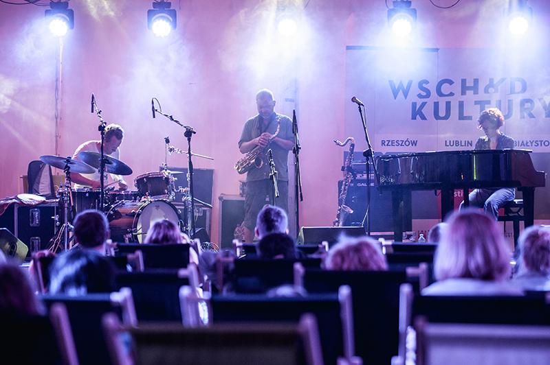 Zdjęcie z koncertu Elisabeth Harnik, Martin Brandlmay, Mikołaj Trzaska. Na scenie troje muzyków, na dole zdjęcia, na leżakach siedzi publiczność.