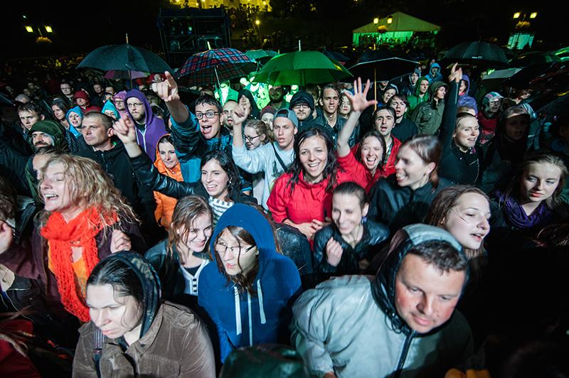 Zdjęcie z koncertu przedstawiające rozśpiewanych, uśmiechniętych młodych ludzi przemoczonych deszczem.
