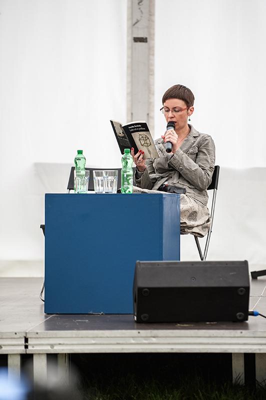 [Na zdjęciu kobieta, która czyta do mikrofonu fragmenty książki. Na pierwszym planie niebieski stolik.]