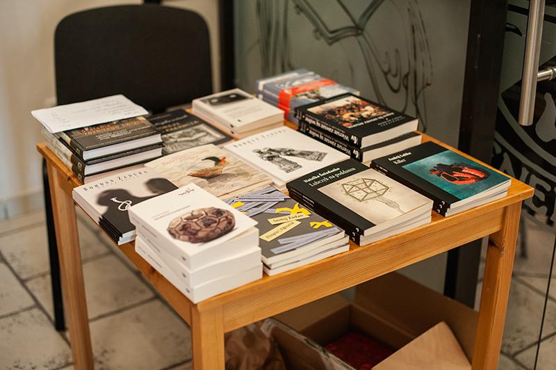[Na zdjęciu widać książki ulożone na drewnianym stoliku]