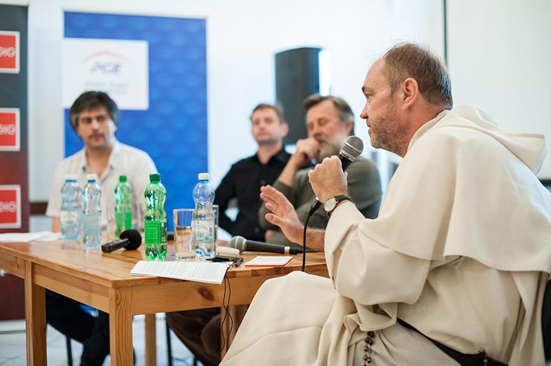 [Zdjęcie z dyskusji. Na pierwszym planie O. Tomasz Dostatni, Dominikanin, w tle pozostali paneliści. Wszyscy mężczyźni siedzą przy drewnianym stole.]