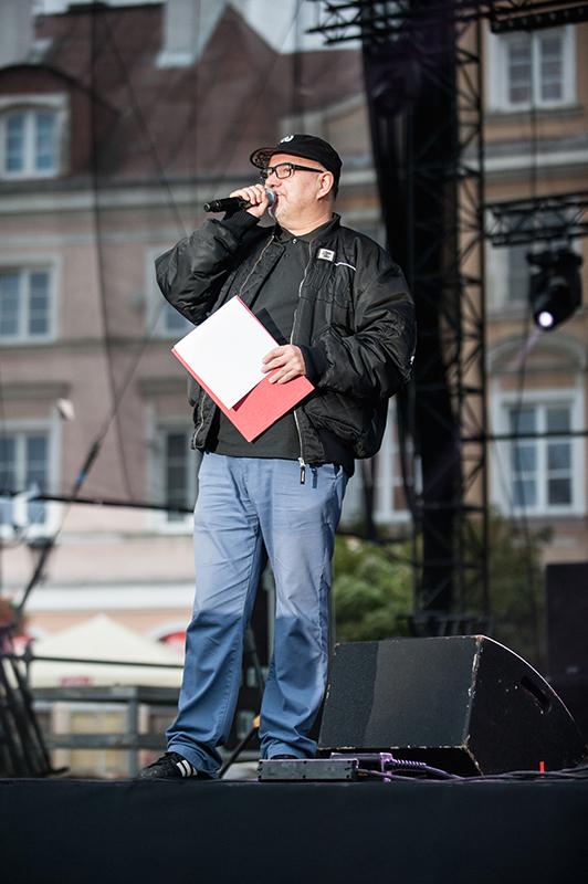 Zdjęcie z festiwalu Wschód Kultury Inne Brzmienia. Na zdjęciu mężczyzna w ciemnej kurtce i dżinsach na scenie, mówi do mikrofonu.