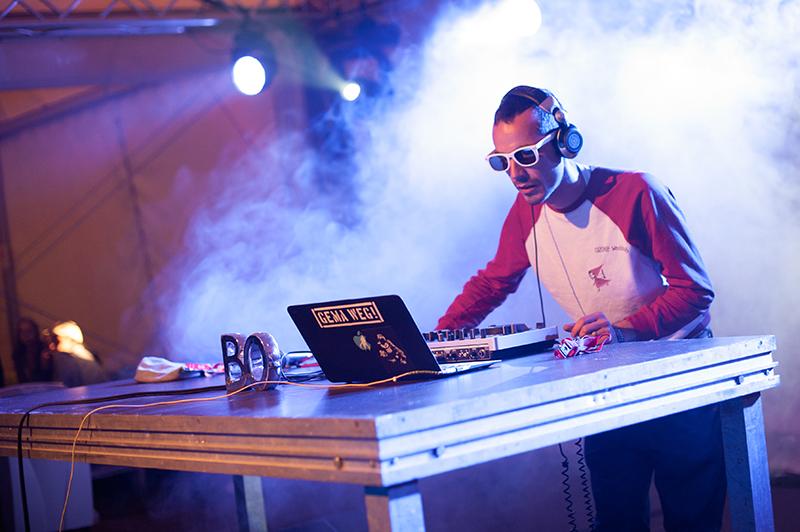 Zdjęcie z koncertu Papa Bo Selektah przedstawiające młodego mężczyznę na scenie, ze słuchawkami na uszach przy sprzęcie do miksowania muzyki