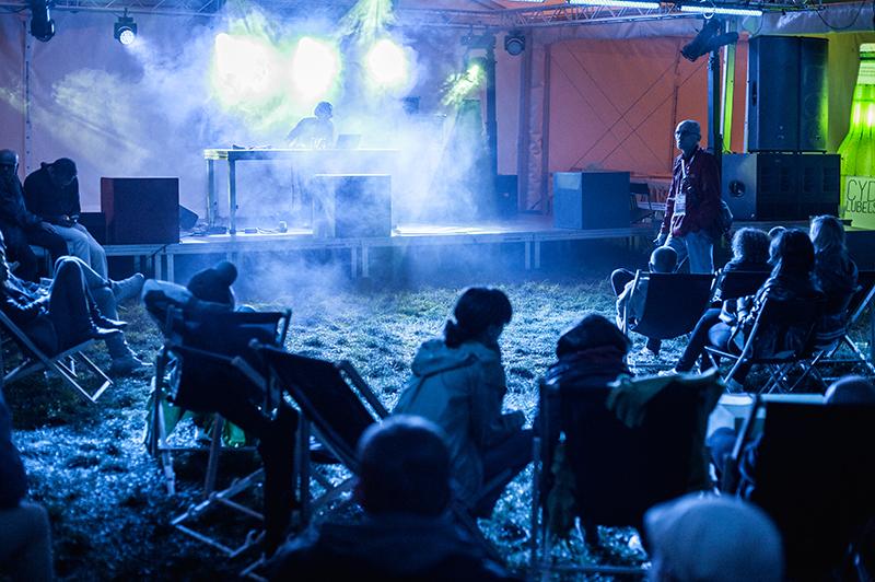 Zdjęcie z koncertu zespołu Papa Bo Selektah przedstawiające na pierwszym planie publiczność na leżąkach, w głębi na scenie mężczyzna spowity mgłą