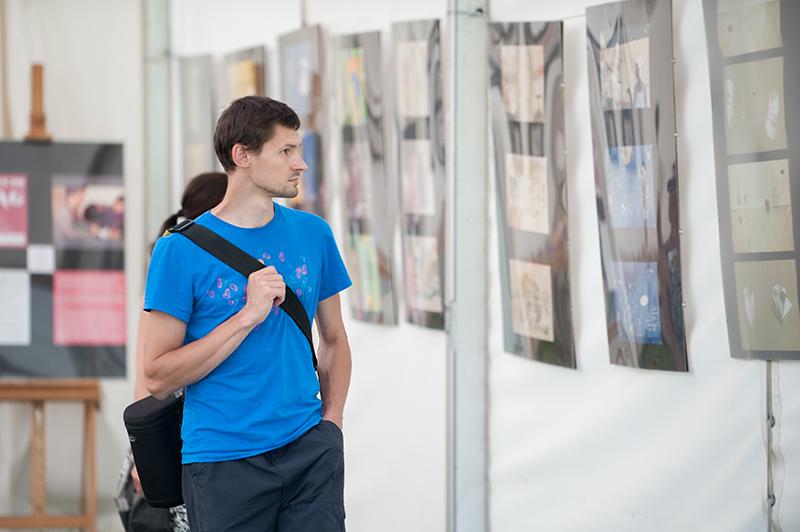 [Zdjęcie przedstawia młodego mężczyznę w niebieskiej koszulce, który ogląda wystawę zaprezentowaną wewnątrz pomieszczenia.]