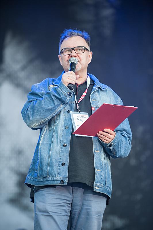 Zdjęcie z festiwalu Wschód Kultury Inne Brzmienia przedstawia Hirka Wronę w dżinsowej koszuli. Mówi do mikrofonu stojąc na scenie, w ręce trzyma czerwoną okładkę na dokumenty.