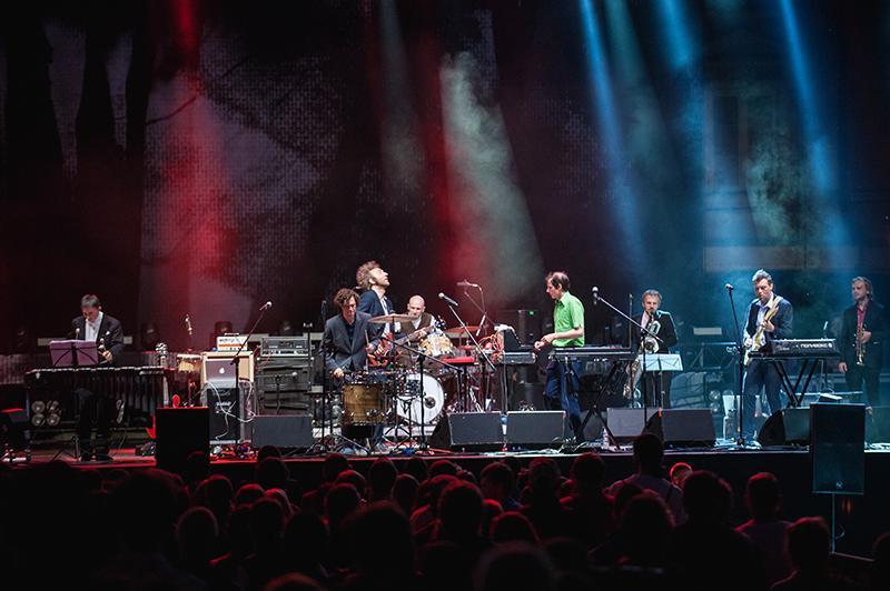 Zdjęcie z koncertu Felix Kubin i Mitch and Mitch, przedstawiające ośmiu mężczyzn grających i śpiewających na scenie. Na dole zdjęcia publiczność.
