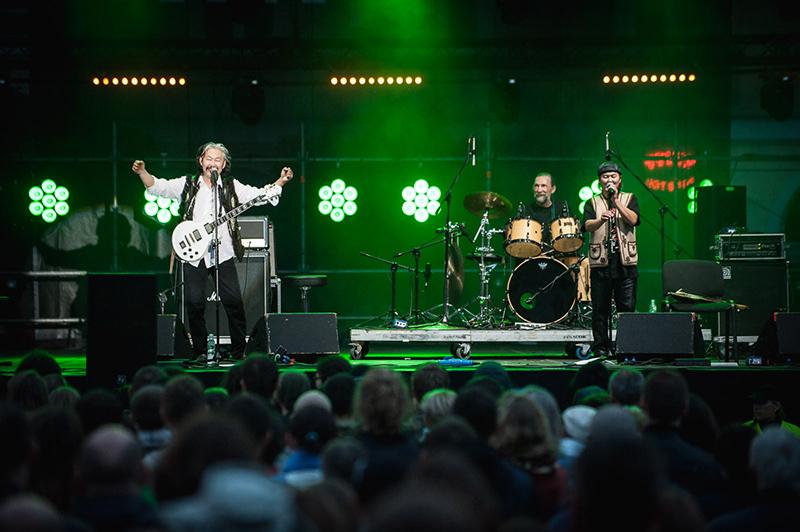 Zdjęcie z koncertu zespołu Yat-Kha. Na zielonej scenie grają i śpiewają muzycy, w dole zdjęcia publiczność.
