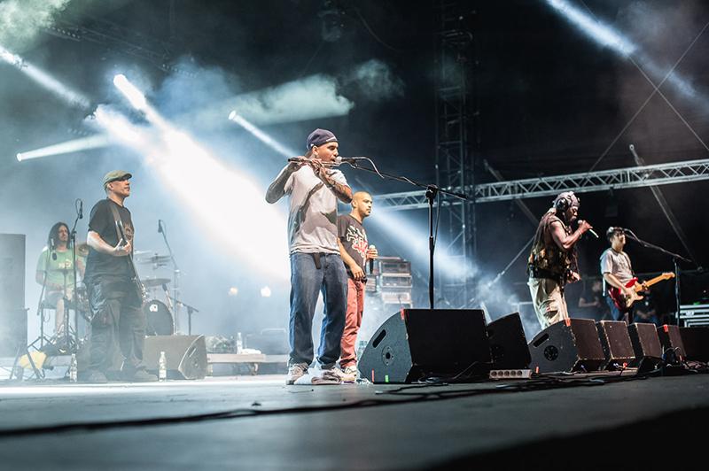 Zdjęcie z koncertu Asian Dub Foundation. Na tle mgły i światła reflektorów muzycy śpiewający oraz grający na perkusji, gitarze i flecie.