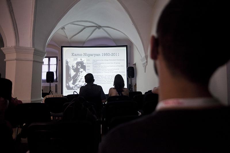 """Zdjęcie z wykłądu i prezentacji """"Nowa Sztuka Ormiańska – pejzaż horyzontalny"""" przedstawiające ekran, na którym widać fragment filmu oraz publiczność."""