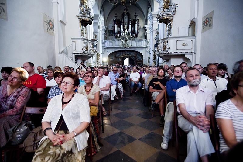 Zdjęcie z koncertu zespołu Lekso Gremelaszwili i Męski Zespół Wokalny KAIROS przedstawiające publiczność, która siedzi w kościele.