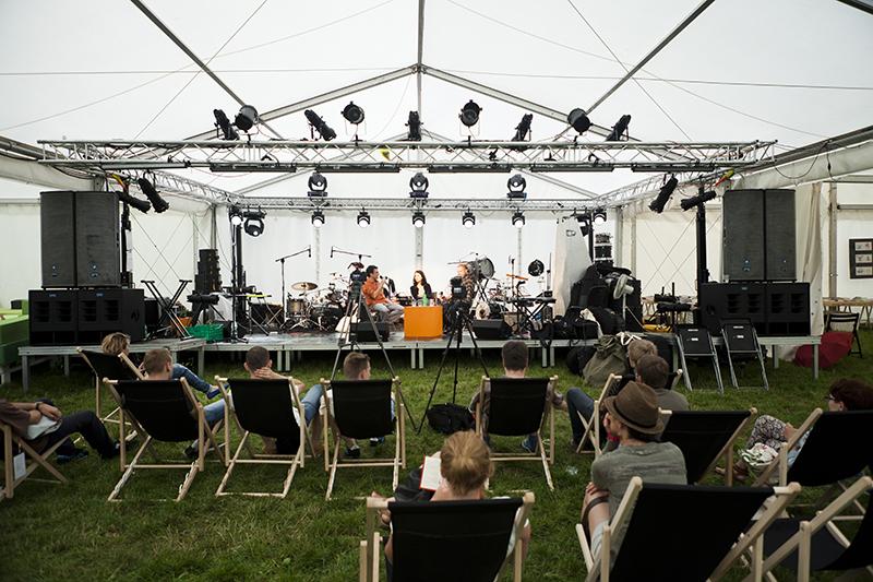 [Zdjęcie z dysusji podczas festiwalu Wschód Kultury Inne Brzmienia. Na pierwszym planie publiczność, która siedzi na czarnych leżakach, na trawniku, pod namiotem. W tle troje panelistów na scenie.]
