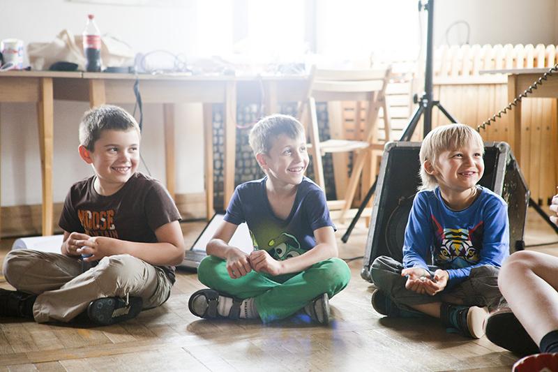 Zdjęcie z Małych Innych Brzmień przedstawiające trzech uśmiechniętych chłoców, którzy siedzą na podłodze.