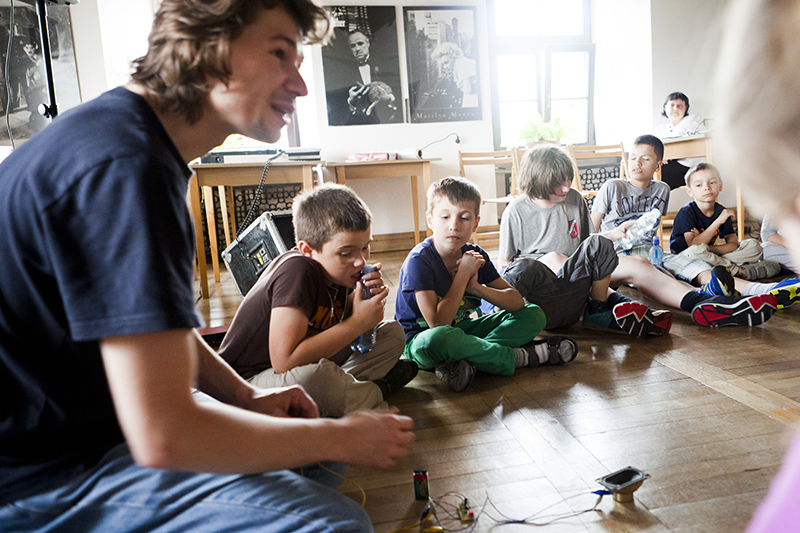 Zdjęcie z Małych Innych Brzmień. Na pierwszym planie siedzi młody mężczyzna i mówi, obok kilku chłopców.