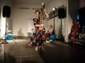 Zdjęcie Laboratorium Sztuki Społecznej. Na pierwszym planie tańcząca kobieta w czerwono-czarnej sukience. W tle inne kobiety.