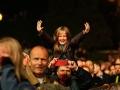 Koncert zespołu Asian Dub Foundation. Publiczność, na pierwszym planie mała uśmiechnięta dziewczynka na ramionach mężczyzny z wyciągniętymi w górę rączkami. Mężczyzna filmuje koncert telefonem komórkowym.