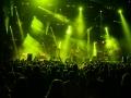 Koncert Asian Dub Foundation. Na pierwszym planie publiczność, która stoi tyłem do obiektywu, a przodem do sceny. Na scenie wśród zielonych świateł gra zespół.