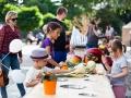 Zdjęcie z Małych Innych Brzmień, na którym dzieci stoją przy długim stole i dotykają warzyw.