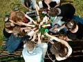 Zdjęcie z Laboratorium Sztuki Społecznej przestawiające kilka kobiet siedzących w kręgu, które wyciągają przed siebie ręce. Zdjęcie zrobione z góry. LSS, fot. R. Pranagal