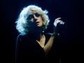 Zdjęcie z koncertu Alison Goldfrapp. Na tle czarnej scenaografii stoi kobieta w ciemnej sukience i jasnych włosach, która śpiewa do mikrofonu.